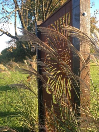 Edelrost Gerbera Sichtschutz in Holzbalken gesetzt
